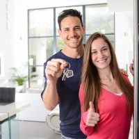 happy young couple at their new house front door proud to show home keys